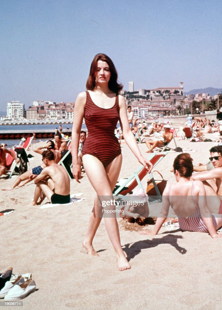 """Christine Keeler, key figure in the 1963 scandal involving Conservative Defence Minister John Profumo, which became known as the """"Profumo Affair"""" walks across the beach in a swimming outfit in Cannes in this 1963 photograph. : News Photo"""
