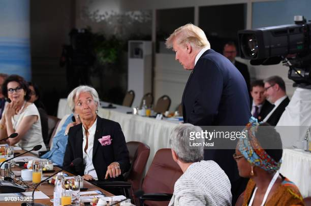 Christine Lagarde looks up at US President Donald Trump as he arrives late to the Gender Equality Advisory Council working breakfast on the second...