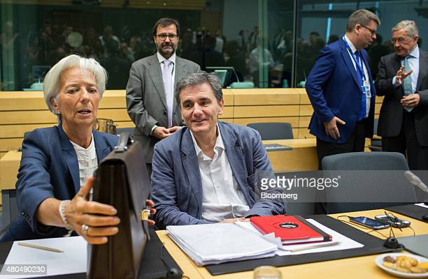 Christine Lagarde managing director of the International Monetary Fund left handles a briefcase as she speaks with Euclid Tsakalotos Greece's finance...