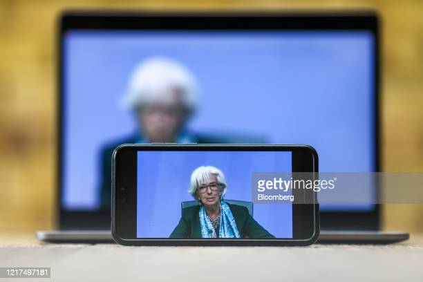Christine Lagarde, president of the European Central Bank , is displayed on a mobile phone and laptop computer during a live stream video of the...