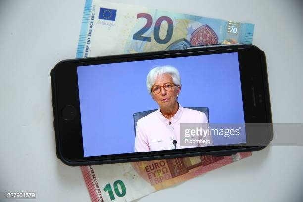 Christine Lagarde president of the European Central Bank is displayed on a smartphone resting on 20 and 10 euro currency banknotes during a live...