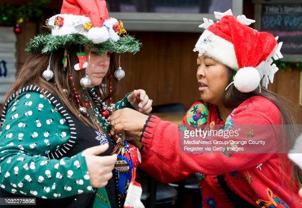 Christine Lyng of Costa Mesa left gets Christmas ornaments attached to her first place Ugliest Christmas Sweater award by Danielle DeMoss for the 2nd...