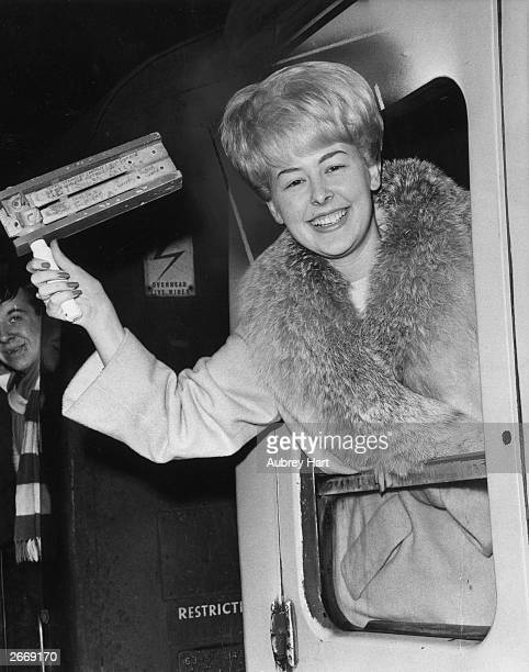 Christine McCann finacee of Chelsea FC captain Terry Venables leans out of a carriage window waving a rattle as she leaves Paddington station on a...