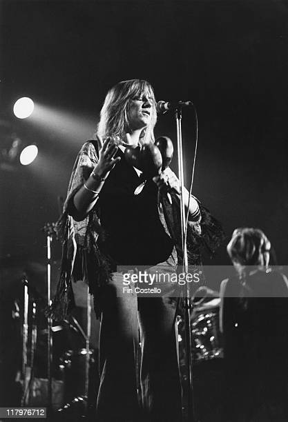 Christine McVie British rock singersongwriter with the band Fleetwood Mac singing into a microphone while holding three shakers in her hand during a...