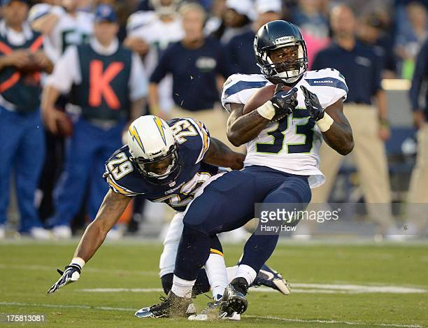 Christine Michael of the Seattle Seahawks attempts to spin away from William Middleton of the San Diego Chargers during the first quarter at Qualcomm...