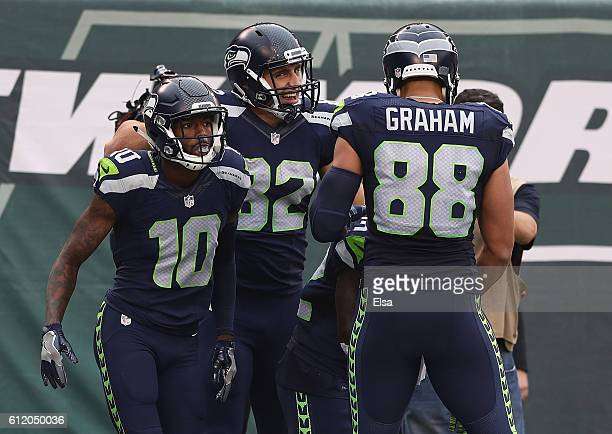 Christine Michael of the Seattle Seahawks is congratulated on his fourth quarter touchdown by teammates Jimmy Graham and Paul Richardson against the...