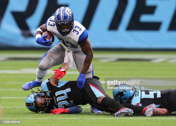 Christine Michael of the St Louis Battlehawks tries to evade Treston Decoud and Reshard Cliett of the Dallas Renegades in the first half of an XFL...
