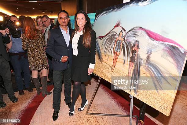 Christine Neubauer and her partner Jose Campos in front of her painting during the 'Christine Neubauer Hautnah' exhibition opening at Hotel Vier...