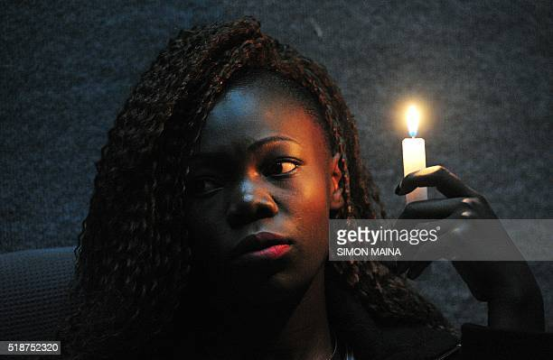 TOPSHOT Christine Ochieng holds a candle on the memorial for the victims of last year's terrorist attack that killed 148 people at the campus of...