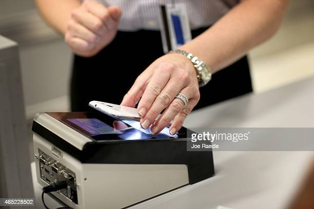 Christine Rolin passes her iphone over a scanner as she uses the new mobile app for expedited passport and customer screening being unveiled for...