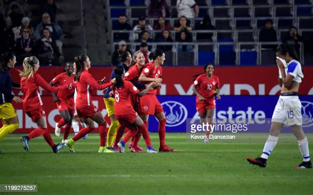 Christine Sinclair of Canada is mobbed by her teammates after defeating Costa Rica 10 and qualifying for the 2020 Olympics in Japan during the...
