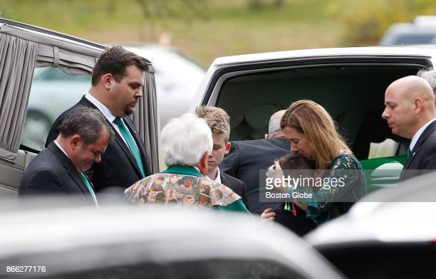 Christine Suau center mother of Devin Suau embraces a child after helping to place Devin's casket in the hearse following his funeral at St Anselm...
