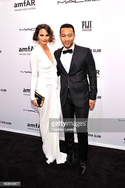 Christine Teigen and John Legend attend the amfAR New York Gala to kick off Fall 2013 Fashion Week at Cipriani Wall Street on February 6 2013 in New...