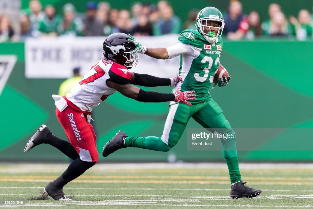 Christion Jones #33 of the Saskatchewan Roughriders gives a straight arm to Tunde Adeleke #27 of the Calgary Stampeders during a run in the second half of the game between the Calgary Stampeders and Saskatchewan Roughriders at Mosaic Stadium on September 24, 2017 in Regina, Canada.