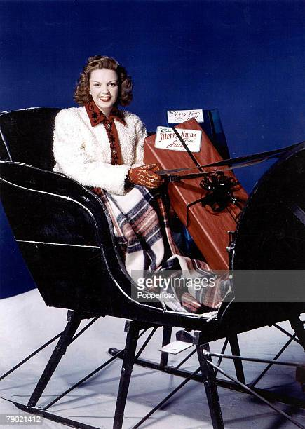 Christmas 1953 A portrait of the American singer and actress Judy Garland sitting in a sleigh with some presents smiling at the camera