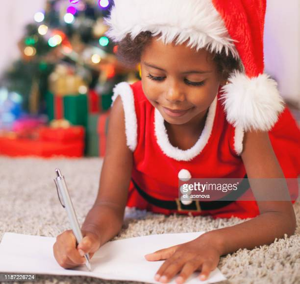 criança afro-americana do natal que escreve uma letra a papai noel - responder - fotografias e filmes do acervo