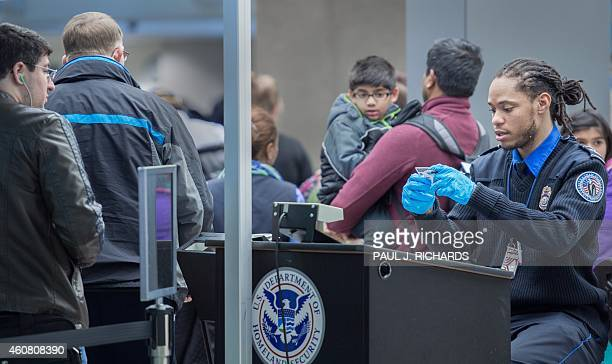 Christmas airline travelers are processed at a Transportation Safety Agency security checkpoint December 23 2014 at Dulles International Airport in...