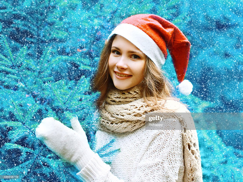 Christmas and people concept - happy girl in red hat : Stock Photo