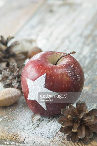 Christmas apple with snow star, pine cones, almonds and hazelnuts on table