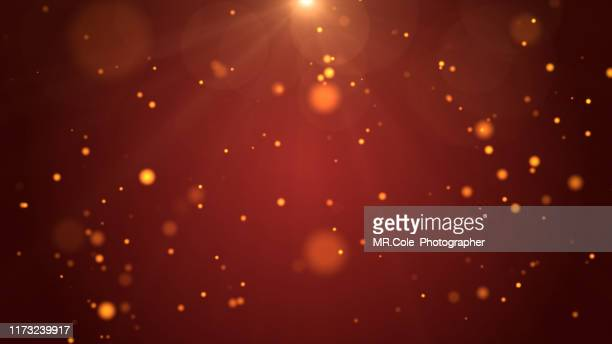 christmas background, de-focused gold colored particles on red background with lens flare - blendenfleck stock-fotos und bilder