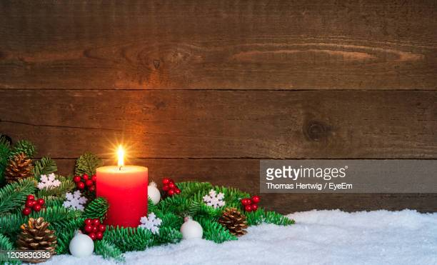 christmas  background with burning red candle on snow, decorated with fir branches and ornaments. - christmas decore candle stock pictures, royalty-free photos & images