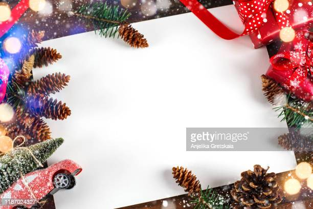 christmas background with fir tree branch, gift boxes and red toy car with christmas tree. - christmas banner stock photos and pictures