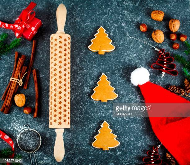 Christmas baking concept. Gingebread cookies, rolling pin, gift box, cinnamon and holiday decoration. Top view.