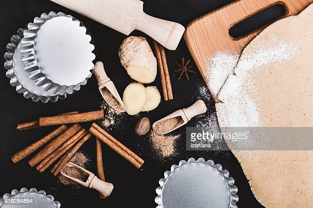Christmas baking ingredients and tolls for dough preparation. Dough, cookie cutters, spices and rustic rolling pin viewed from above