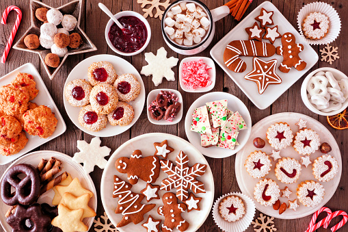 Christmas baking table scene with assorted sweets and cookies, top view over a rustic wood background 1185515984