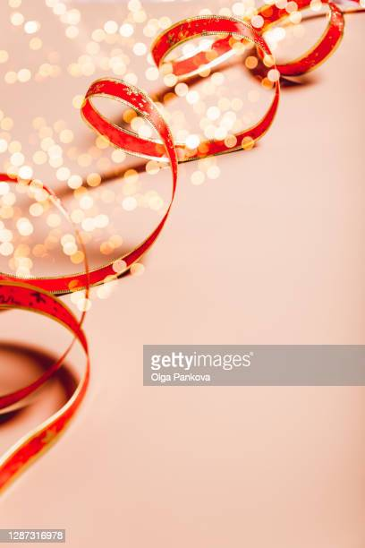 christmas beige and red background. red decoration tape and christmas lights on a cream color backdrop. close up. - maroon stock pictures, royalty-free photos & images