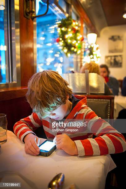 Christmas, boy on cell phone in restaurant