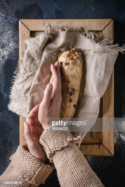 Christmas cake Female hands make traditional German festive baking Wholegrain dough stollen preparation on linen napkin over dark blue texture...