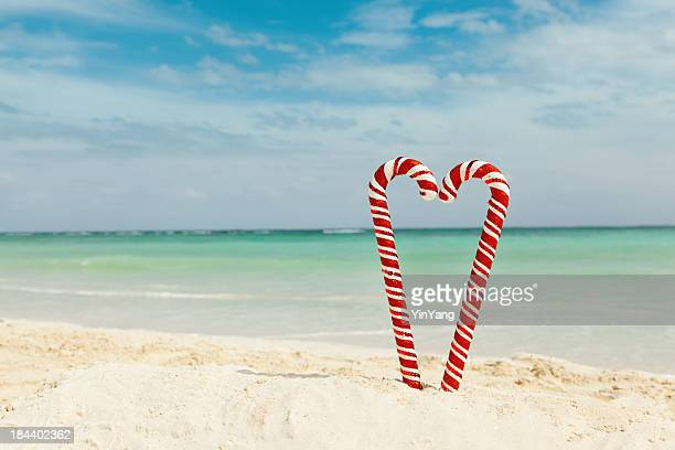 christmas candy canes heart on tropical caribbean sandy beach hz - caribbean christmas stock pictures, royalty-free photos & images