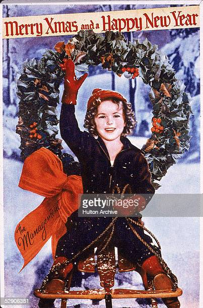 Christmas card or promotional portrait of American child actress Shirley Temple who rides on a sled and waves 1930s
