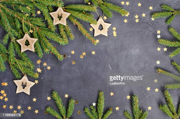 christmas card with fir branches, wooden star decoration, gold confetti on dark background - friday stock pictures, royalty-free photos & images