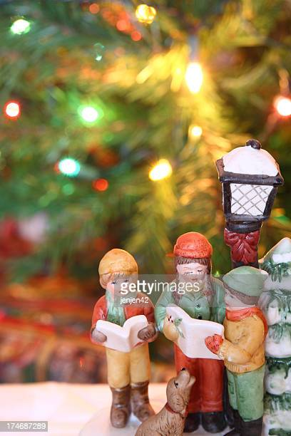 Christmas carolers figurines over a Christmas background