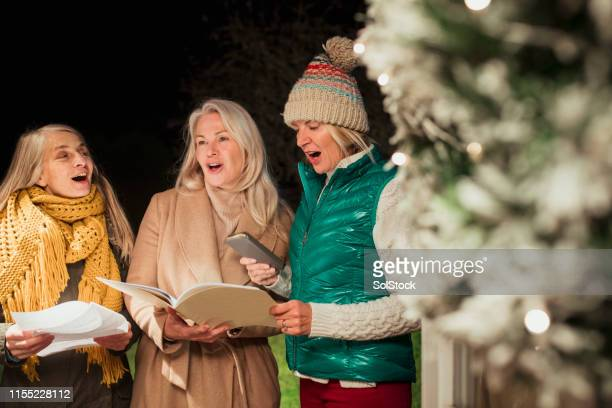 christmas caroling - choir stock pictures, royalty-free photos & images