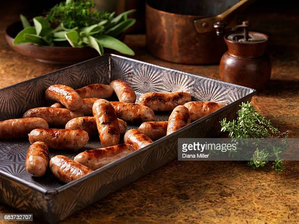 christmas, celebration food, classic cocktail sausage selection, in baking tray, fresh thyme and sage - sausage stock pictures, royalty-free photos & images
