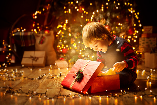 Christmas Child Open Present Gift, Happy Baby Boy looking to Magic Light in Box, Kid and Xmas Tree 1063239772