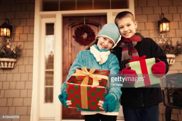 Enfants debout avec des cadeaux de Noël et vous présente à la porte
