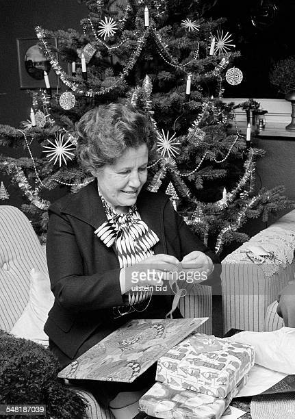 Christmas, Christmas Eve, older woman on unpacking the Christmas presents, in the background the Christmas tree, aged 60 to 70 years, Frieda -