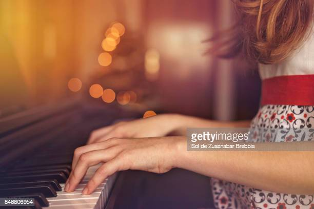 christmas. close up of the hands of a girl playing the piano. - pianoforte foto e immagini stock