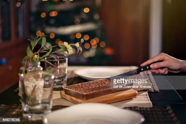 christmas. close-up of a hand cutting a chocolate nougat with christmas lights behind - nougat stock pictures, royalty-free photos & images
