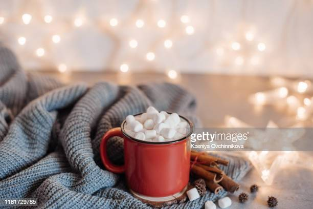 christmas cocoa header with marshmallows, chocolate crumbs, and syrup. large coffee cup with homemade hot chocolate. winter drink photography on a dark background - hot chocolate stock pictures, royalty-free photos & images