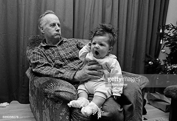 'Christmas Comes but once a Year ' A grandfather holds his tired granddaughter at armslength while watching a television prgramme at Christmas time...