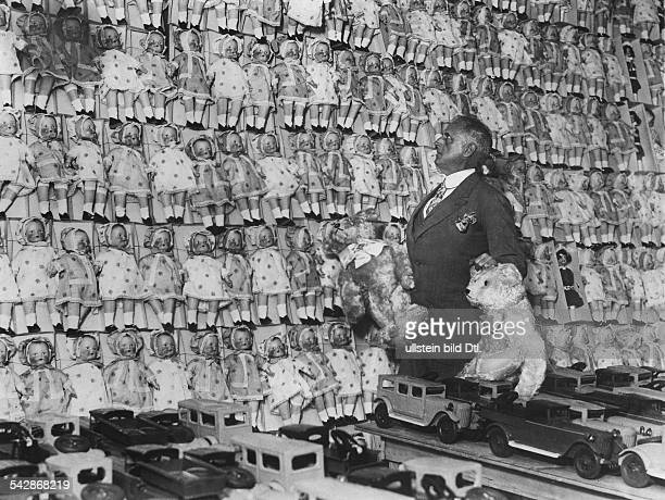 Christmas coming soon A salesman with two teddy bears in front of a wall of dolls 1929 Photographer Dephot Published by 'Tempo' Vintage property of...