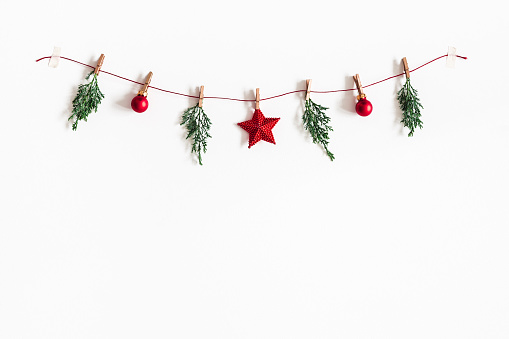 Christmas composition. Garland made of red balls and fir tree branches on white background. Christmas, winter, new year concept. Flat lay, top view, copy space 1064023690