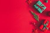 Christmas composition. Gift box, christmas decorations on red background. Flat lay, top view, copy space