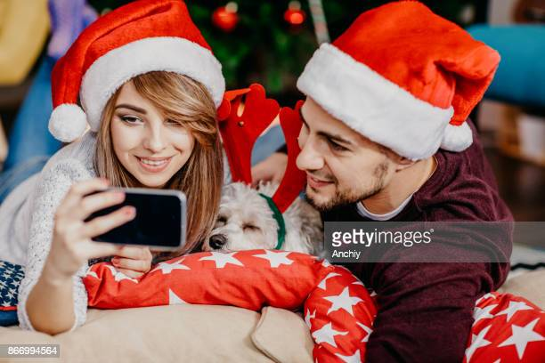 Christmas concept of young couple taking selfie with santa's hats