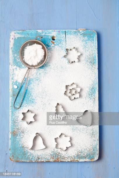 christmas cutters and a sieve with icing sugar - rua stock pictures, royalty-free photos & images
